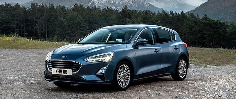 Ford Focus parkerad på bergsväg vid barrskog
