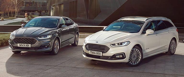 Två Ford Mondeo parkerade vid anlagd trädgård